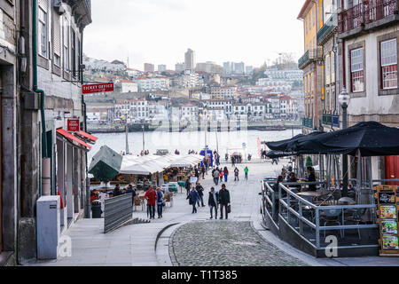 Porto, Portugal - December 2018: Ribeira Square during the day, with people walking and view to Douro River. - Stock Photo