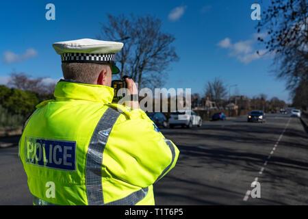 Traffic police officer holding a radar speed camera at an urban speed control checkpoint in Edinburgh, Scotland UK - Stock Photo