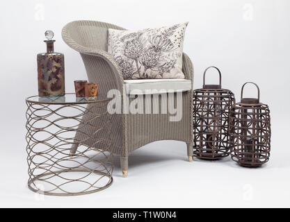 Wicker chair and cushions with a side table and two wicker candle holder on a white background - Stock Photo