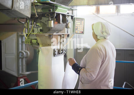 14 october 2014.Ukraine.Kyiv. The woman of average years in a white dressing gown works on a conveyor at factory of times of the Soviet, manual skills - Stock Photo