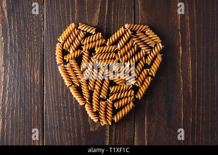 Heart shaped pasta on dark wooden background - Stock Photo