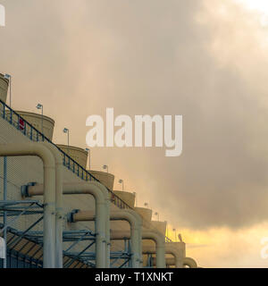 Building of Power Plant emitting steam at sunset. Building with pipes and ridges on the wall at a Power Plant in Utah Valley. Gray steam from the buil - Stock Photo