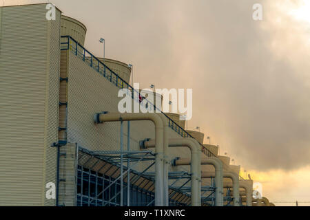 Thick gray steam from a Power Plant in Utah Valley. Building at a Power Plant in Utah Valley emitting thick gray steam into the sky. Large pipes are c - Stock Photo