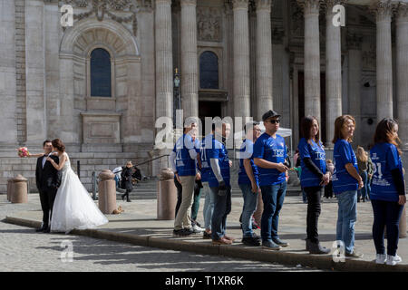 A Chinese wedding couple stand outside St. Paul's Cathedral alongside some Asian corporate achievers, on 25th March 2019, in London, England. - Stock Photo