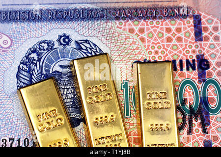 A macro image of an Uzbek ten thousand som bank note with three gold bars close up - Stock Photo