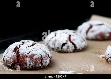 Chocolate cookies with cracks on baking paper and iolated on black. Cracked chocolate biscuits. - Stock Photo