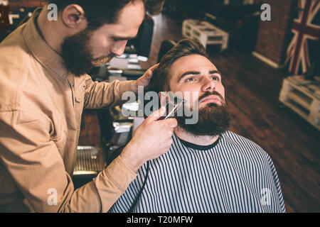 Nice and good hairstylist is cutting some of the customer's beard with an electrical razer. He is doing that very accurate - Stock Photo