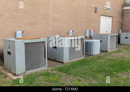 Commercial Air Conditioner compressors outside of brick building - Stock Photo