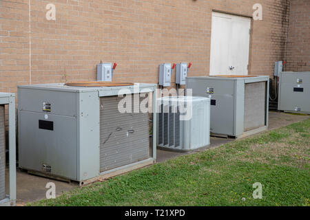 Multiple Commerical Air Conditioner Compressors outside brick building - Stock Photo