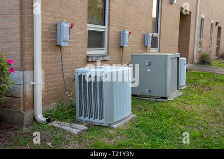 Multiple Air Conditioner Compressors outside brick building - Stock Photo