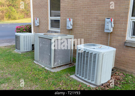 3 Air Conditioner Compressors outside commercial building with cutoff switches. - Stock Photo