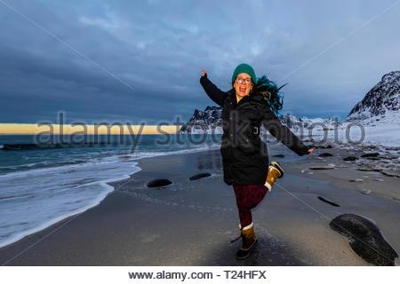 Young woman enjoying the winter landscape at Uttakleiv Beach, Vestavagoya Island, Lofoten Islands, Arctic, Northern Norway. - Stock Photo