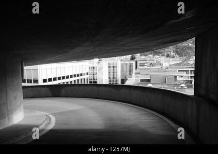View through an architectural frame of some buildings in Lugano (Switzerland) from a parking lot - Black and white picture - Stock Photo