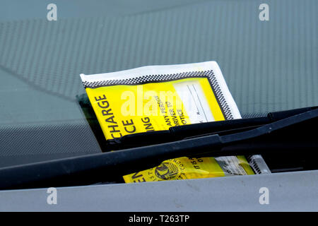 Fixed charge parking notice on a windscreen under a winds screen wiper - Stock Photo