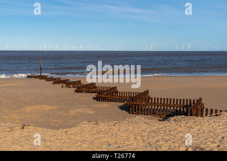 North sea coast in Caister-on-Sea, Norfolk, England, UK - with a wave breaker and wind turbines in the background - Stock Photo