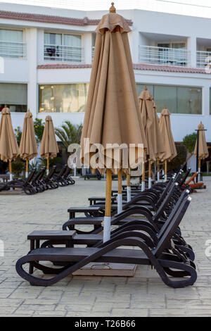 Several rows of empty beach loungers near the hotel swimming pool under closed umbrellas. Beach lounges, leaving in perspective. Empty sun loungers in - Stock Photo