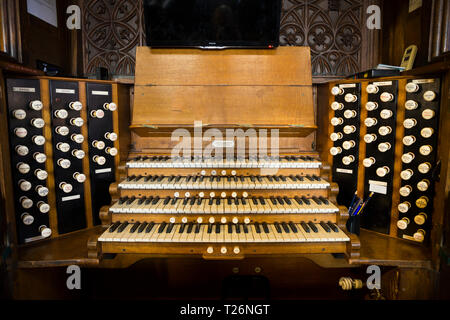 Organ (musical instrument ) and its keys / keyboard in Halifax Minster. The organ stops are visible on either side. West Yorkshire. UK. It was made by Harrison and Harrison of Durham UK - Stock Photo