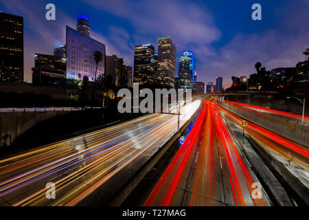 JANUARY 20, 2019, LOS ANGELES, CA, USA - California 110 South leads to downtown Los Angeles with streaked car lights at sunset - Stock Photo