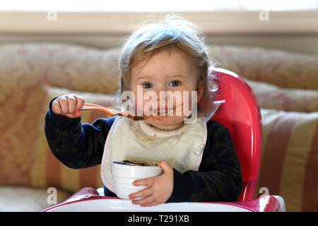 Baby girl feeding herself with chocolate on her face - Stock Photo
