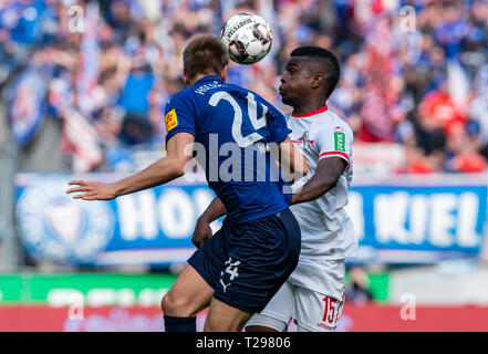 Cologne, Germany. 31st Mar, 2019.  Soccer: 2nd Bundesliga, 1st FC Cologne - Holstein Kiel, 27th matchday in the Rhein-Energie-Stadion. Cologne's Jhon Cordoba (r) and Kiel's Hauke Wahl fight for the ball. Photo: Guido Kirchner/dpa - IMPORTANT NOTE: In accordance with the requirements of the DFL Deutsche Fußball Liga or the DFB Deutscher Fußball-Bund, it is prohibited to use or have used photographs taken in the stadium and/or the match in the form of sequence images and/or video-like photo sequences. Credit: dpa picture alliance/Alamy Live News - Stock Photo
