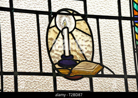 Stained glass window showing book and candle - Stock Photo