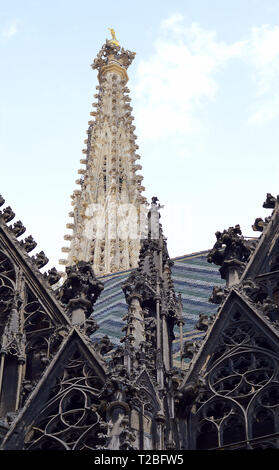 The magnificent south tower of the Stephansdom (St Stephen;s cathedal) rises above gothic tracery and the mosaic tiled roof in Vienna, Austria - Stock Photo