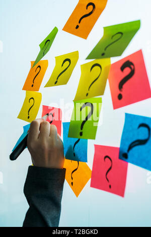 Businesswoman writing question marks on colorful sticky note paper on office whiteboard, selective focus - Stock Photo