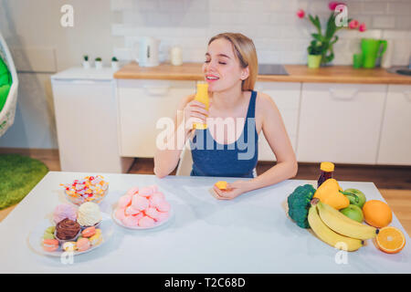 Young smiling woman drinks detox water while choosing between healthy and unhealthy food in the kitchen. Difficult choice between fresh fruit - Stock Photo