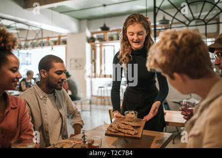 Smiling waitress bringing a food order to a group of young friends eating together in a bistro - Stock Photo