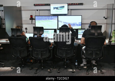 31 March 2019, North Rhine-Westphalia, Köln: Football Bundesliga - video evidence, visit to the Video Assist Center during live football Bundesliga coverage. Video assistants and technicians sit in front of their screens. Photo: Henning Kaiser/dpa - Stock Photo