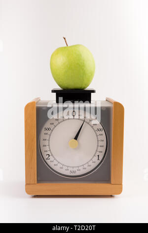vintage wooden kitchen scales isolated on white background  with green apple - Stock Photo