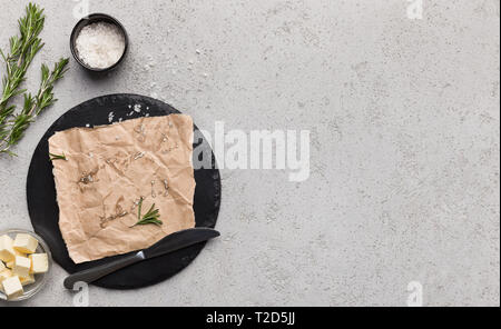 Cubes of butter in bowl rosemary leaves and craft paper on board over concrete background, top view, copy space. Spicy butter recipe mockup - Stock Photo