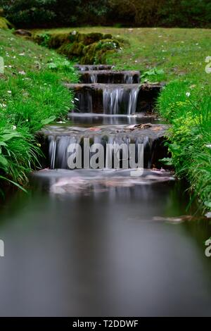 Long exposure of a series of mini waterfalls in an ornamental stream - Stock Photo