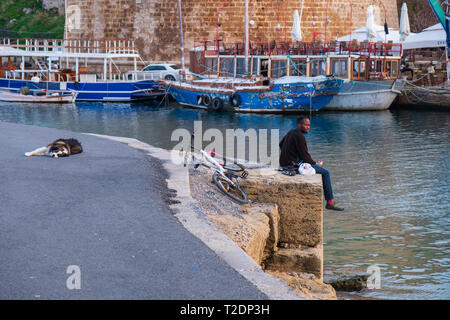 Kyrenia, Cyprus - November 27, 2018: An african man sits by the sea at the old harbor of Kyrenia in Cyprus whilst a dog near him is sleeping on the ta - Stock Photo