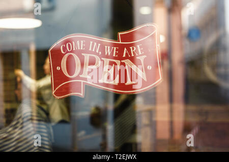 Business vintage sign that says Come in We're Open on barber and hair salon shop window - Image of abstract blur barbershop with people in the backgro - Stock Photo