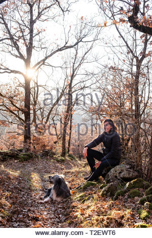 Woman with her dog in the forest enjoying sunset time. - Stock Photo