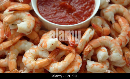 A plate of fresh shrimp with a bowl of cocktail sauce - Stock Photo