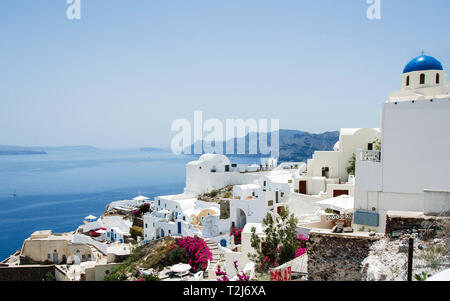 A beautiful, classic Orthodox church sits on the cliffside of Santorini, overlooking the Aegean Sea. - Stock Photo