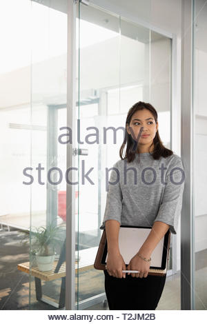 Confident, ambitious businesswoman standing in office - Stock Photo