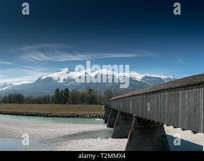 old wooden covered bridge crossing the Rhine river from Liechtenstein to Switzerland with a great view of the Swiss Alps in spring under a blue sky - Stock Photo