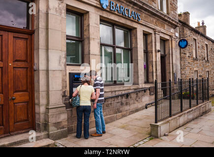 A branch of Barclays Bank set in the rural village of Middleton in Teesdale,England,UK with man and woman at cash dispenser - Stock Photo