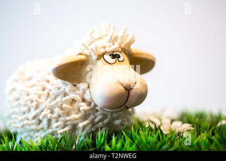 A small statue of a white sheep placed on grass. This decoration can be used for Easter celebrations. - Stock Photo