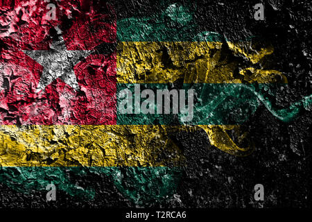 Togo smoky mystical flag on the old dirty wall background - Stock Photo