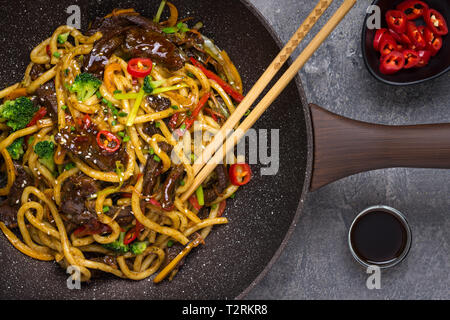 Udon Stir-Fry Noodles with Beef and Vegetables in Wok Pan on Dark Background - Stock Photo
