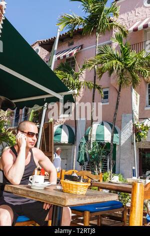 Miami Beach Florida Espanola Way restaurant sidewalk cafe coffee cup al fresco alfresco Hispanic man cell phone sunshine tank to - Stock Photo