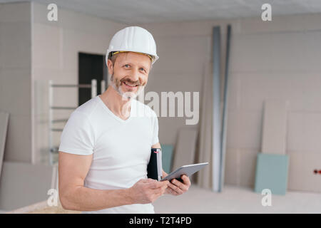 Confident happy builder or handyman wearing a hardhat in a new build house holding a tablet and journal as he smiles at the camera - Stock Photo