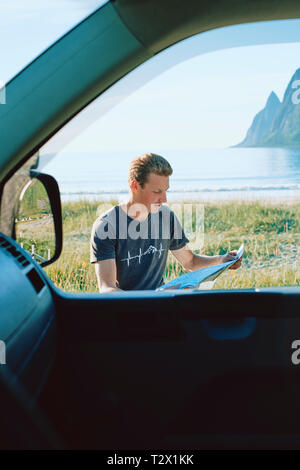 A location portrait of a young man reading a map and route planning outside of his car at the coast. - Stock Photo