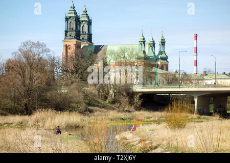 Two men fishing in a river in front of the cathedral of St Peter and St Paul on Ostrow Tumski island in the Polish city of Poznan Poland - Stock Photo