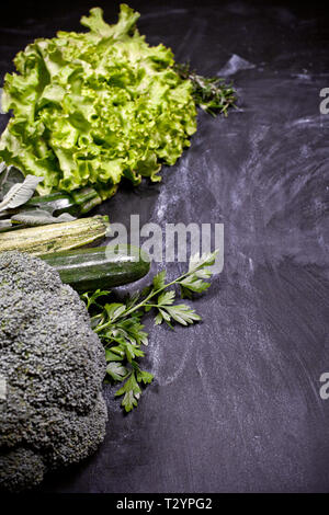 Variety of green vegetables and herbs. Clean eating food concept. On blackboard background with copy space. - Stock Photo