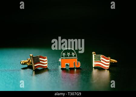 Emblem of the american republican party, an elephant, between two flags USA, isolated on black background. - Stock Photo